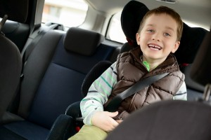 Happy little boy in car safety seat. Children car safety concept